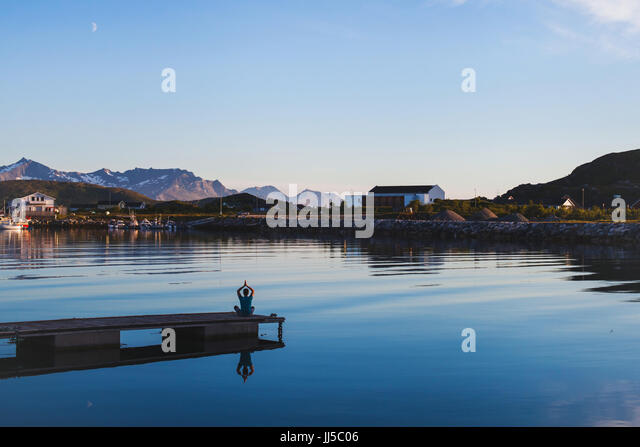yoga and meditation background, silhouette of man relaxing on the pier on lake - Stock Image
