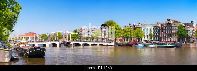 The Magere Brug ('Skinny Bridge') in Amsterdam over the River Amstel on a beautiful sunny day - Stock Image