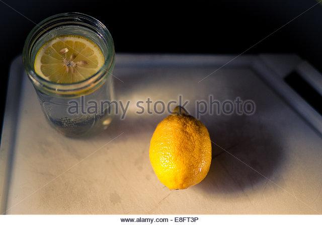 Glass of lemon water and lemon on tray - Stock-Bilder