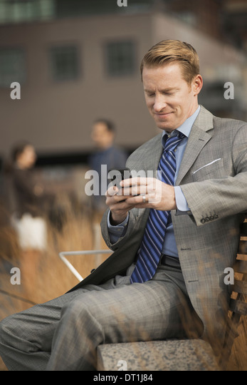 A man sitting on a bench outside a large building looking at a cell phone screen or mobile phone - Stock Image