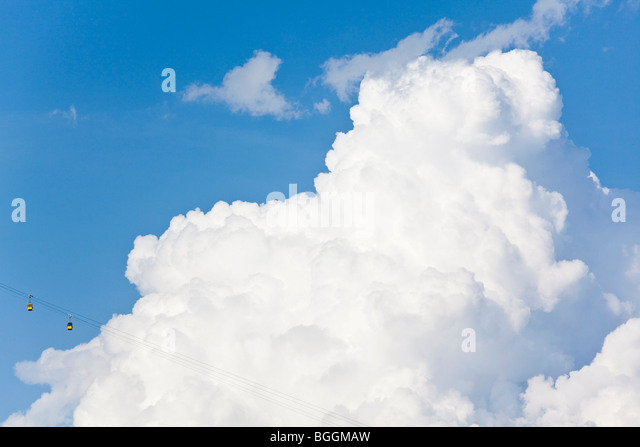 Cable cars in front of a cumulus cloud, Zillertal, Austria, low angle view - Stock Image