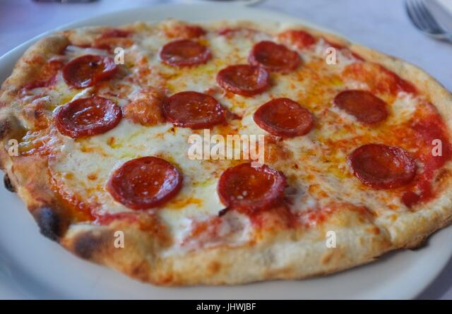 A pepperoni pizza on a table at a restaurant in the lower city, Bergamo, Lombardy, northern Italy, July 2017 - Stock Image