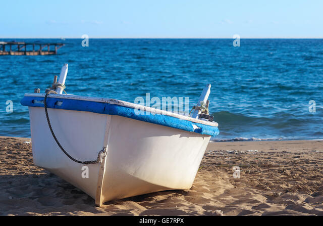 Old white rowing boat on sandy beach with blue sky and sea coastal background. - Stock Image