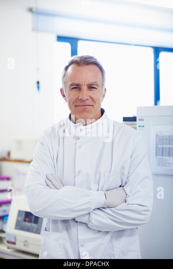 Portrait of researcher standing in lab wearing lab coat - Stock Image