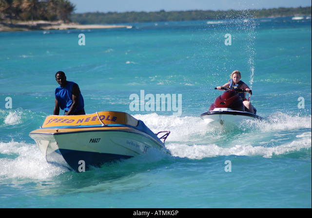 Jet skier and speedboat, Long Bay Beach, Antigua - Stock Image