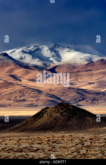 Small cinder cone and snow covered mountains Black Rock Desert National Conservation Area Nevada - Stock Image