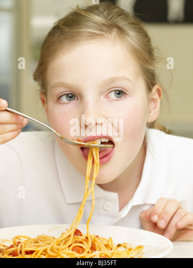 A Girl eating pasta - Stock Image