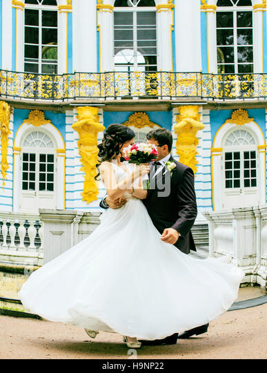 very beautiful bride with groom hugging and dancing at blue palace, lifestyle people concept - Stock Image
