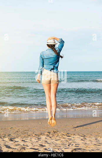 Pretty woman jumping on the beach. - Stock Image
