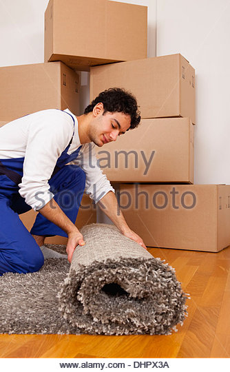 young man new home moving in out rolling carpet - Stock Image