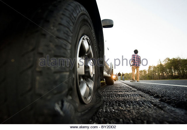 A man  with a flat tire stands on a highway with. - Stock Image