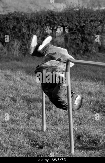 young kid child boy playing on playground equipment climb climbing frame net exercise balance energy hyperactive - Stock Image