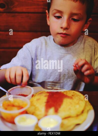 Boy Having Pancakes In Restaurant - Stock-Bilder