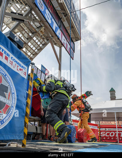 Competing firefighters start their run up a four story tower. - Stock Image