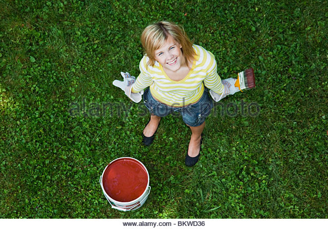 Girl on grass with red paint - Stock-Bilder