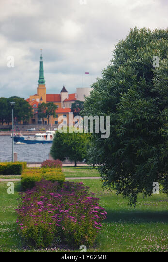 Quay with trees and flowers in the park against the backdrop of the presidential palace in Riga in summer - Stock Image