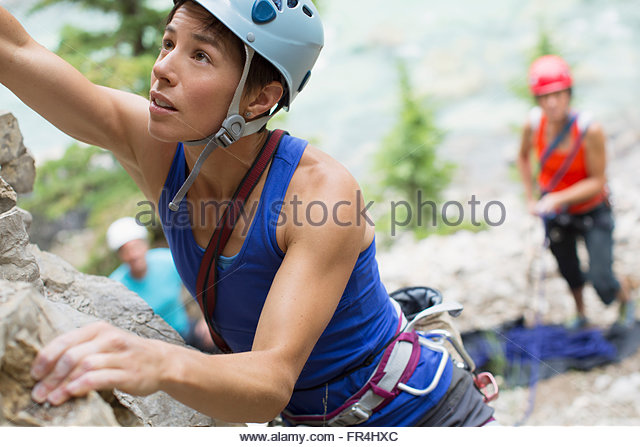 rock climbers watching female climber going up rock face - Stock Image