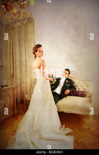 Full length of bride and groom in luxurious and with a vintage look interior with dress seen from the rear - Stock Image