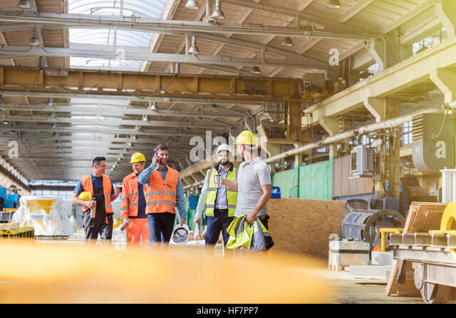 Steel workers walking and talking in factory - Stock Image