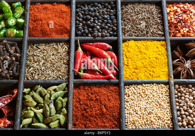 Indian cooking spices in an old wooden tray. Flat lay photography from above - Stock Image