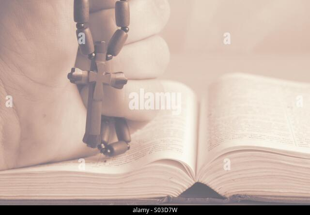 Wooden Christian cross in his hand on the bible. - Stock Image