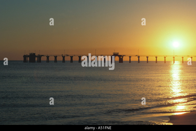 Sunset ocean long fishing pier - Stock Image