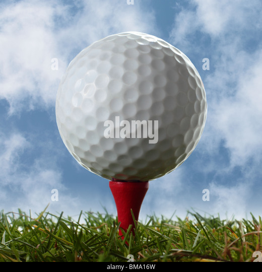 Close up of golf ball on red tee above real grass with cloudy blue sky behind - Stock Image