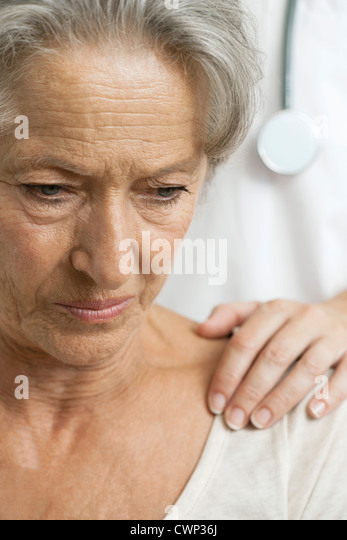 Senior woman receiving bad news from caring doctor, cropped - Stock Image
