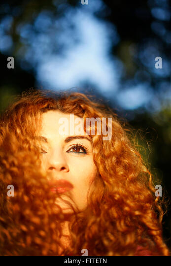 Curly woman closeup in golden hour - Stock Image