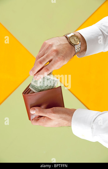 man places dollar into wallet - Stock Image