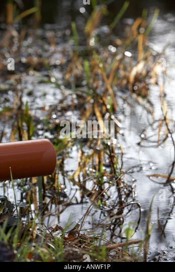 plastic water overflow pipe sticking out into river - Stock Image