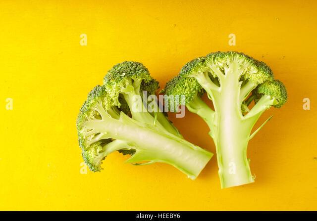 Fresh broccoli on a yellow table horizontal - Stock Image