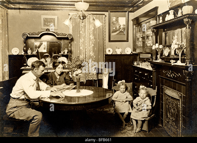 Couple with Twins Looking at Photograph Album - Stock-Bilder