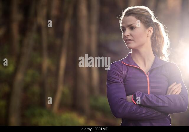 Young woman in forest arms folded looking away - Stock Image
