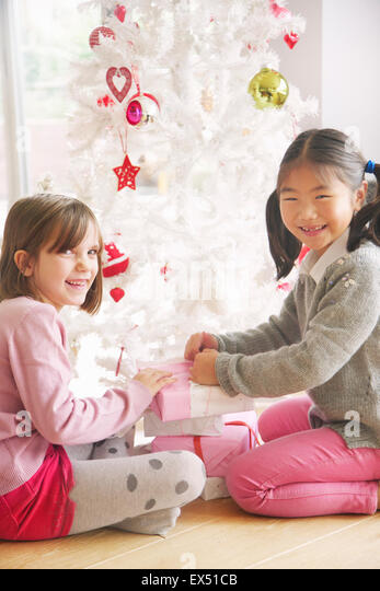 Two Young Girls Opening Presents under Christmas tree, Smiling - Stock Image