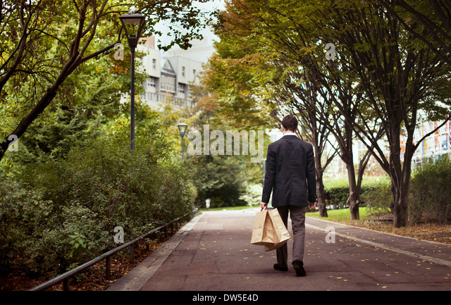 solitude, lonely man with shopping bags walk after work - Stock-Bilder