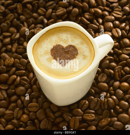 A cup of coffee cappuccino style with a heart shape on the top, shot on coffee beans. - Stock Image