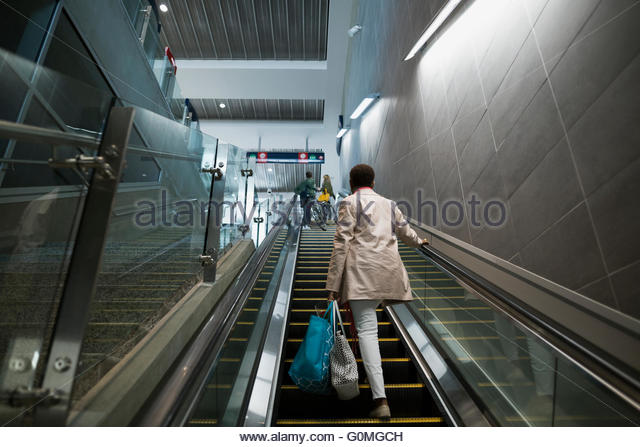 Woman ascending escalator at train station - Stock Image