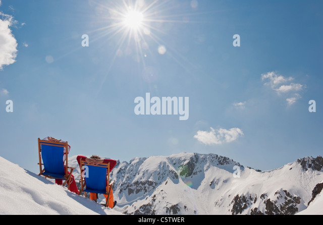 Austria, Salzburger Land, Couple sitting in deck chairs, rear view - Stock Image