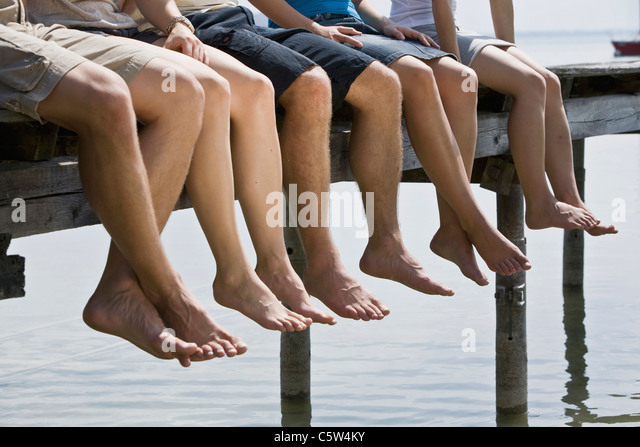 Germany, Bavaria, Five persons sitting on jetty, low section - Stock Image