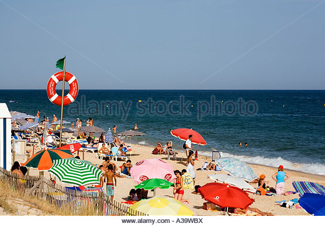 Portugal eastern Algarve Praia Da Barril Illha de Tavira sand beach people life belt sunshades - Stock Image