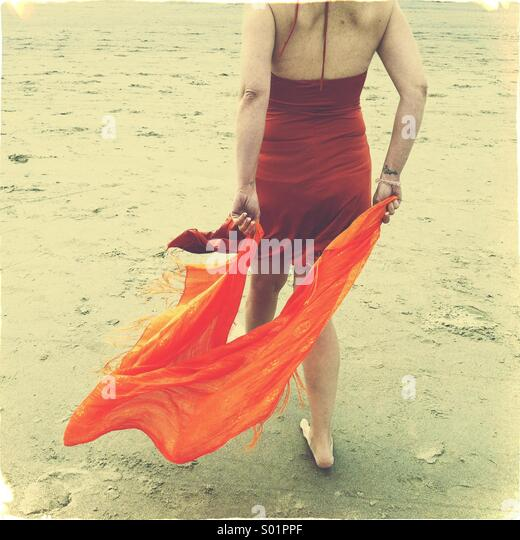 woman walking on beach with scarf - Stock Image