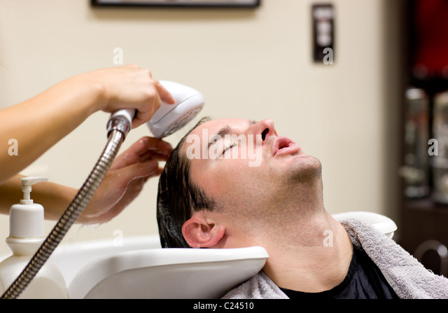 Young man having his hair washed - Stock-Bilder