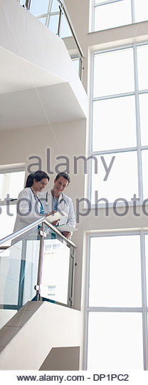 Doctors discussing paperwork on stair - Stock Image