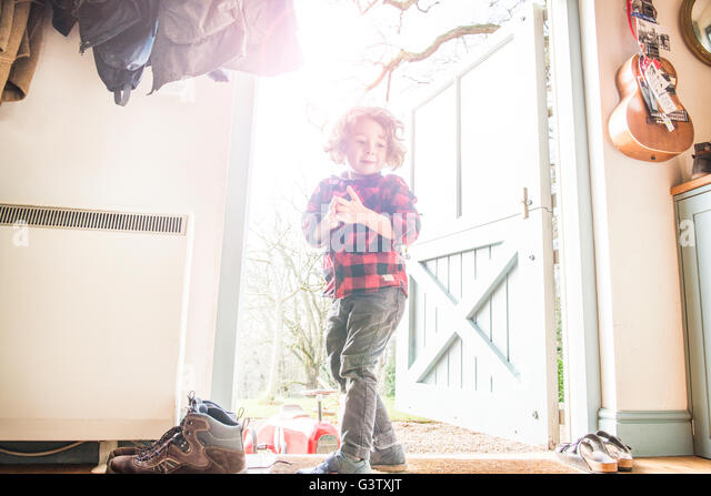 A four year old boy standing at an open back door in a check shirt. - Stock Image