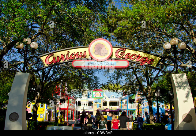 Curious George Goes To Town attraction sign and tourists at Universal Studios Orlando Florida - Stock Image