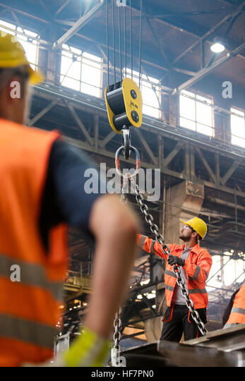 Steel workers operating crane in factory - Stock Image