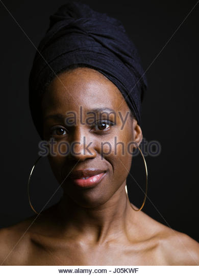 Portrait confident African American woman wearing headscarf and hoop earrings against black background - Stock Image