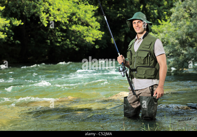 A young fisherman posing with fishing pole in his hand on a river - Stock Image