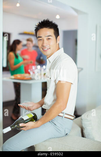 Man holding bottle of wine at party - Stock Image